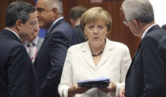 **FILE** German Chancellor Angela Merkel (center) speaks June 29, 2012, with European Central Bank President Mario Draghi (left) and Italian Prime Minister Mario Monti during a round-table meeting at a EU Summit in Brussels. (Associated Press)