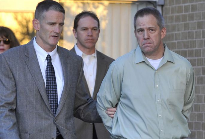 **FILE** Clayton Frederick Osbon (right), the JetBlue pilot who disrupted a flight by running through the plane and yelling about terrorists, is escorted April 2, 2012, to a waiting vehicle by FBI agents as he is released from The Pavilion at Northwest Texas Hospital, in Amarillo, Texas. (Associated Press/Amarillo Globe-News, Michael Schumacher)