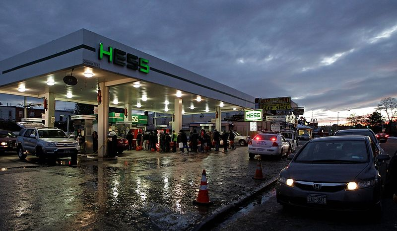 People with plastic containers and cars wait in line Nov. 8, 2012, for gasoline at a Hess station in the Brooklyn borough of New York. Fuel shortages and distribution delays that occurred after Superstorm Sandy and a nor'easter hit the region led to gas hoarding, prompting New York City and Long Island to initiate an even-odd gas rationing plan. (Associated Press)