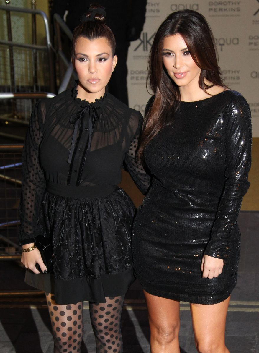 Kim (right) and Kourtney Kardashian arrive for their Kardashian Kollection UK Launch at Acqua Club in central London on Nov. 8, 2012. (Joel Ryan/Invision/Associated Press)