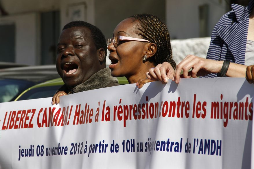 Sadio Balde (left), vice president of the Moroccan Council for Sub-Saharan migrants, joins dozens of Moroccan and foreign activists in a protest Nov. 9, 2012, outside a court in Rabat, Morocco, where Council president Laye Camara is being tried for illegally selling alcohol and cigarettes. Colleagues of Camara say the charges are trumped-up and are part of a widespread crackdown on legal and illegal black African migrants to this North African kingdom that lies just across the narrow Straits of Gibraltar from Europe. (Associated Press)