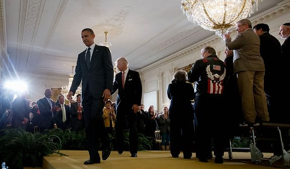 President Obama, followed by Vice President Joe Biden, walks off stage Nov. 9, 2012, after speaking in the East Room of the White House in Washington about the economy and deficit. (Associated Press)