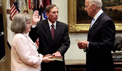 **FILE** Holly Knowlton Petraeus holds the family bible as her husband, David Petraeus, is sworn in by Vice President Joe Biden as CIA Director on Sept. 6, 2011, in the Roosevelt Room of the White House in Washington. (Associated Press)