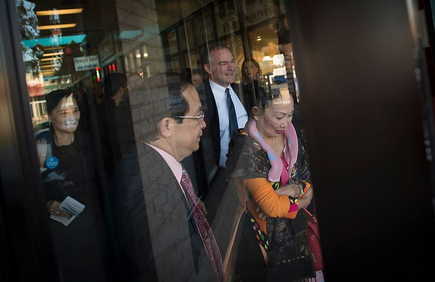 Democratic U.S. Senate candidate and former Virginia Governor Tim Kaine (center) is joined by Anh Hong Do (left) and Kim-Ha Ly (right) as he arrives to meet customers and business owners at the Eden Center in Falls Church, Va., Sunday, Nov. 4, 2012. (Rod Lamkey Jr./The Washington Times)