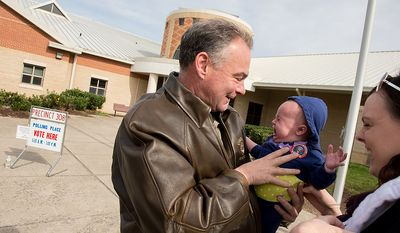 Sarah Baker of Richmond, Va., right, laughs as her five month old  daughter Wila begins to cry in the arms of democratic candidate for Senate Tim Kaine, as they chat together outside the polling entrance at Linwood Holton Elementary School on election day morning, Richmond, Va., Tuesday, November 6, 2012. (Andrew Harnik/The Washington Times)