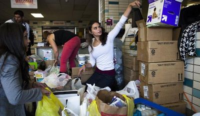**FILE** Volunteer Jamie d'Amico, 25, of Fort Lee, helps sort through donations at Hoboken High School in Hoboken, N.J., on Nov. 4, 2012, as surrounding neighborhoods remain without power due to damage caused by Superstorm Sandy. (Associated Press)