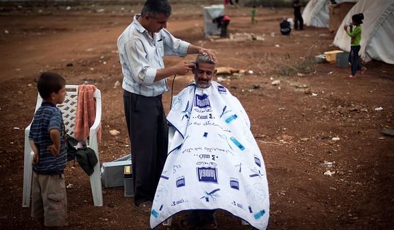 A Syrian man who fled from the violence in his village sits Nov. 8, 2012, for a haircut next to his tent at a camp in the Syrian village of Atmeh, near the Turkish border. (Associated Press)