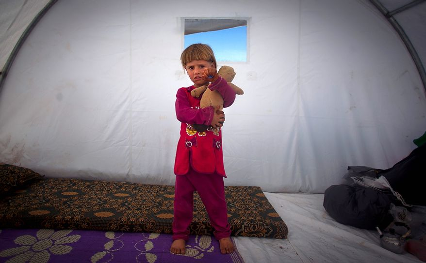 Amina Al Sado, 5, who fled with her family from the violence in their village, poses Nov. 7, 2012, for a photograph inside a tent at a displacement camp in the Syrian village of Atmeh, near the Turkish border. (Associated Press)