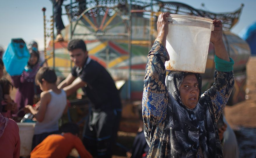 A Syrian woman who fled from the violence in her village carries a water bucket on her head Nov. 7, 2012, at a displacement camp in the Syrian village of Atma, near the Turkish border. (Associated Press)