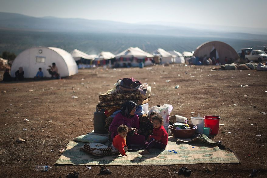 A Syrian family who fled from the violence in their village sits next to their belongings Nov. 7, 2012, at a displacement camp in the Syrian village of Atma, near the Turkish border. (Associated Press)