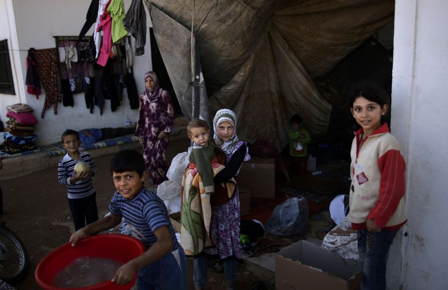 **FILE** Syrian children, who fled their homes due to government shelling, take refuge Sept. 13, 2012, with their families at Bab Al-Salameh crossing border, hoping to cross to one of the refugee camps in Turkey, near the Syrian town of Azaz. (Associated Press)