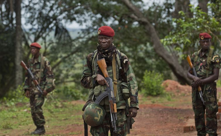 **FILE** Troops from the Central African Republic stand guard April 29, 2012, at a building in Obo, Central African Republic, used for joint meetings between them and U.S. Army special forces, where U.S. special forces have paired up with local troops and Ugandan soldiers to seek out Joseph Kony's Lord's Resistance Army (LRA). (Associated Press)