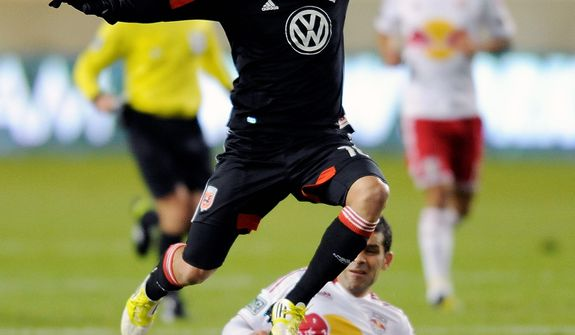 D.C. United midfielder Nick DeLeon (top) leaps over New York Red Bulls defender Rafa Marquez during the first half of an MLS Eastern Conference semifinal playoff soccer game on Nov. 8, 2012, in Harrison, N.J. (Associated Press)