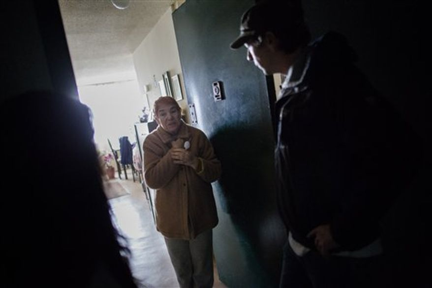 Lysya Fridlin, 76, a resident of the Sand Castle houses, speaks to volunteers who are delivering food and supplies as she continues to live without power in the Far Rockaways section of the Queens borough of New York, Saturday, Nov. 10, 2012. Despite power returning to many neighborhoods in the metropolitan area, residents of the Far Rockaways continue to live without power and heat due to damage caused by Superstorm Sandy.(AP Photo/John Minchillo)