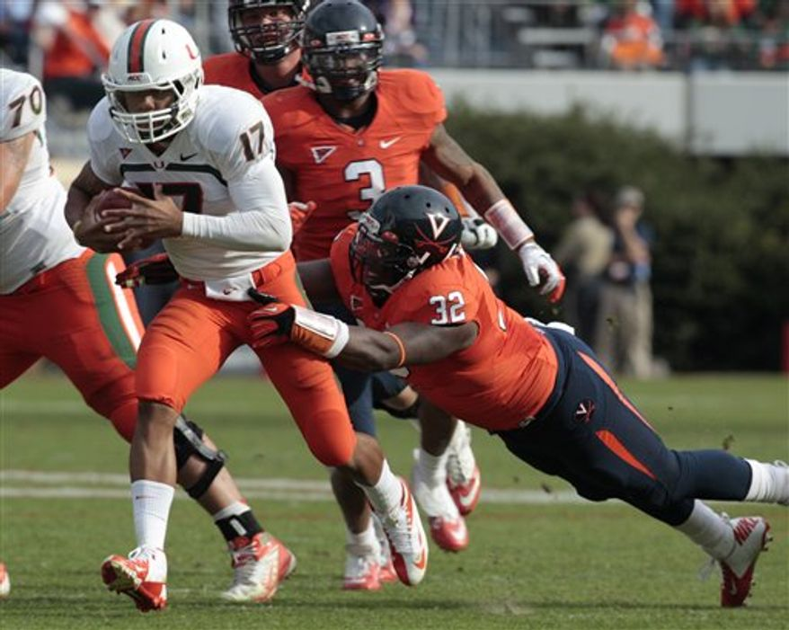 Miami quarterback Stephen Morris (17) tries to elude the tackle of Virginia defensive end Mike Moore (32) during the second half of an NCAA college football game in Charlottesville, Va., Saturday, Nov. 10, 2012. Virginia won 41-40. (AP Photo/Steve Helber)