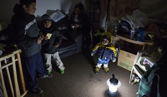 Living through another night of possibly freezing temperatures, Michael Pineda, 15 months old, stands bundled up near a battery-operated lantern in his home without power or heat in the Rockaway Park neighborhood in the Queens borough of New York, Thursday, Nov. 8, 2012, in the wake of Superstorm Sandy. From left is his brother Mario Pineda, 12, Walter Rivera, 5, and center in deep shadow is their mother Fatima Pineda. (AP Photo/Craig Ruttle)