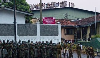Sri Lankan inmates shout from a roof of a prison building as prison guards assist an injured colleague, foreground right, outside a prison in Colombo, Sri Lanka, Friday, Nov. 9, 2012. (AP Photo/Gemunu Amarasinghe)
