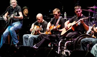 ** FILE ** In this Nov. 11, 2012, file photo, Roger Waters (left), formerly of Pink Floyd, performs with injured service members at the sixth annual Stand Up For Heroes benefit concert in New York. (Associated Press)