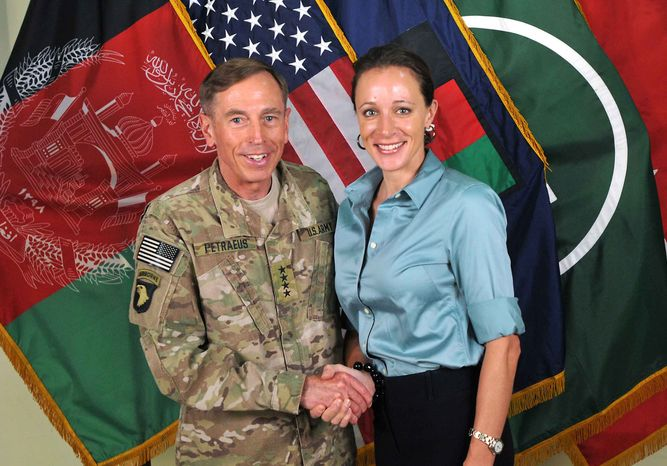 """This July 13, 2011, photo made available on the International Security Assistance Force's Flickr website shows the former Commander of International Security Assistance Force and U.S. Forces-Afghanistan Gen. Davis Petraeus, left, shaking hands with Paula Broadwell, co-author of """"All In: The Education of General David Petraeus.""""As details emerge about Petraeus' extramarital affair with his biographer, Broadwell, including a second woman who allegedly received threatening emails from the author, members of Congress say they want to know exactly when the now ex-CIA director and retired general popped up in the FBI inquiry, whether national security was compromised and why they weren't told sooner. (AP Photo/ISAF)"""