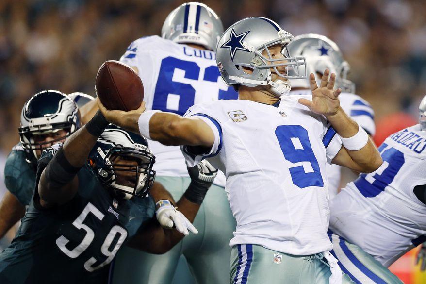 Dallas Cowboys quarterback Tony Romo, right, passes under pressure from Philadelphia Eagles middle linebacker DeMeco Ryans in the first half of an NFL football game, Sunday, Nov. 11, 2012, in Philadelphia. (AP Photo/Julio Cortez)