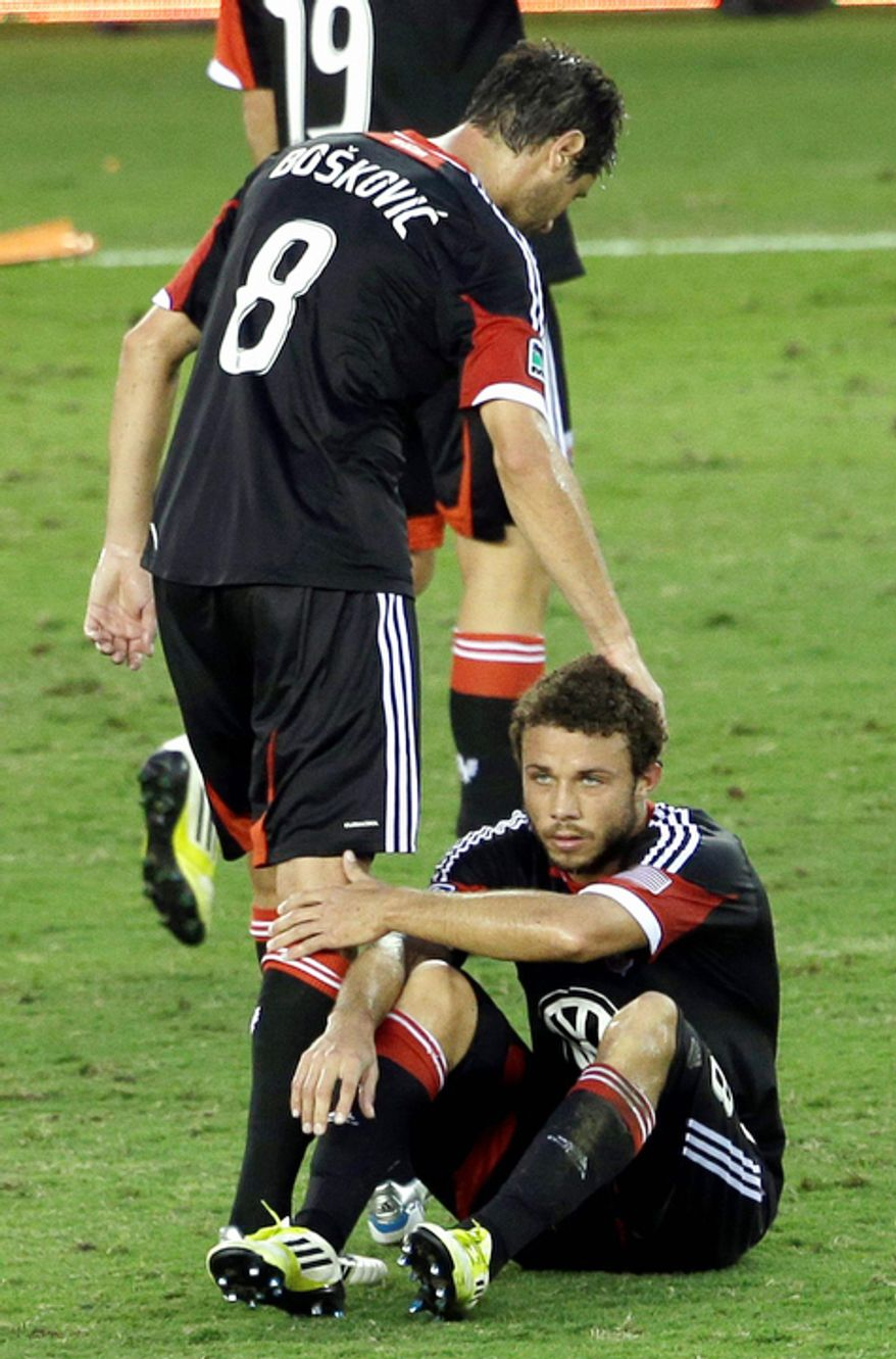D.C. United's Branko Boskovic (8) pats the head of Nick DeLeon after losing to the Houston Dynamo in an MLS Eastern Conference Championship soccer game, Sunday, Nov. 11, 2012, in Houston. The Dynamo defeated D.C. United 3-1. (AP Photo/David J. Phillip)