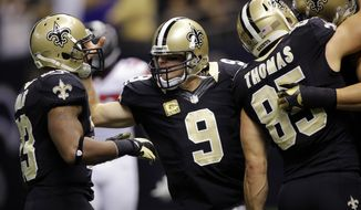 New Orleans Saints quarterback Drew Brees (9) celebrates a touchdown pass with running back Pierre Thomas (23) and tight end David Thomas (85)in the first half an NFL football game against the Atlanta Falcons at Mercedes-Benz Superdome in New Orleans, Sunday, Nov. 11, 2012. (AP Photo/Bill Haber)