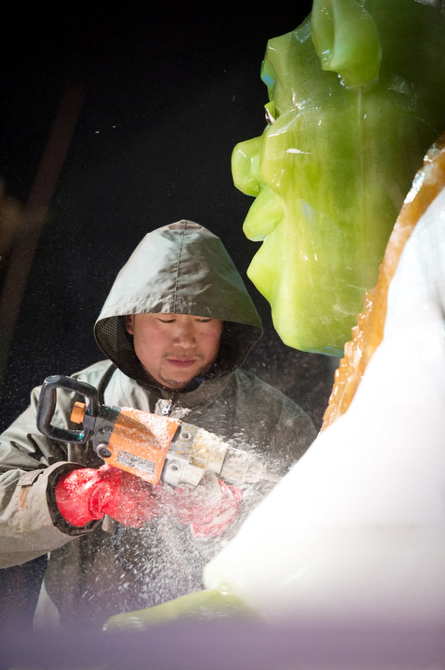 An artisan ice sculptor from Harbin, China, puts the final touches on a ice sculpture of Shrek at the attraction ICE! featuring DreamWorks Shrek the Halls at the Gaylord National Resort & Convention Center in National Harbor, Md., Friday, Nov. 9, 2012.  (Rod Lamkey Jr./The Washington Times)