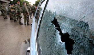 Lebanese Army soldiers are seen near a damaged car in the southern port city of Sidon, Lebanon, on Nov. 11, 2012. Security officials said shooting between Sunni and Shiite Muslim gunmen in southern Lebanon killed one person and wounded at least three. (Associated Press)