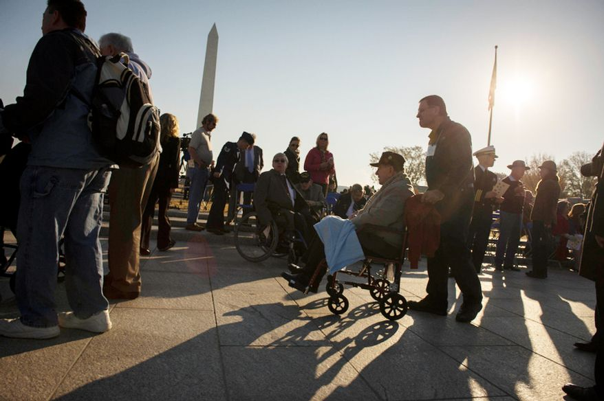 World War II veterans arrive as the sun rises during the Veterans Day at the National World War II Memorial event in Washington, D.C. (Rod Lamkey Jr./The Washington Times)