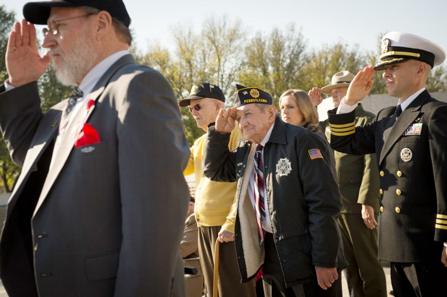 US Navy Gunner's Mate 3rd Class (Retired) Leo Stanley Zawislak (center) salutes during Taps at the Veterans Day at the National World War II Memorial event. (Rod Lamkey Jr./The Washington Times)