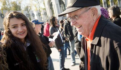 National Park Service volunteer Kimberly Saucedo-Broach,16, chats with World War II veteran US Navy Coxwain (Retired) Barney Melvin, of Shelbyville, Ill., (right) during the Veterans Day at the National World War II Memorial event in Washington, D.C. (Rod Lamkey Jr./The Washington Times)