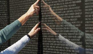 People point to names on the Vietnam Veterans Memorial on Veterans Day, Sunday, Nov. 11, 2012, in Washington. (Rod Lamkey Jr./The Washington Times)