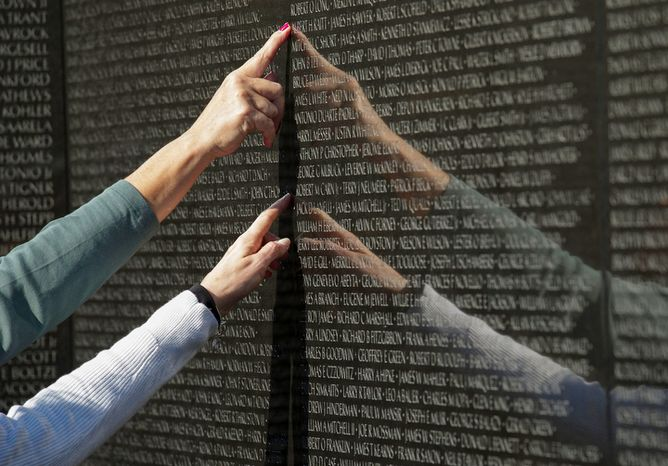 People point to names on the Vietnam Veterans Memorial on Veterans Day, Sunday, Nov. 11, 2012, in Washington. (Rod Lamkey Jr./The Washington Times)