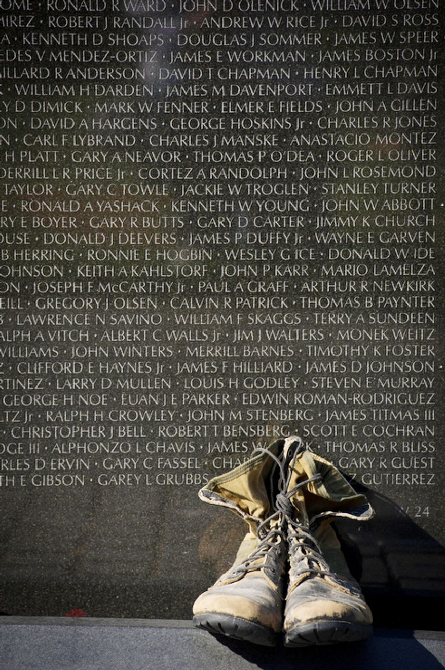 A pair of combat boots lat the the foot of one of the wall panels of names at the Vietnam Veterans Memorial during Veteran's Day weekend. (Rod Lamkey Jr./The Washington Times)