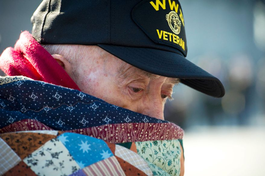 US Navy Petty Officer 3rd Class and Seabee (retired) Leon Clifton of Mt. Zion, Ill., is bundled up against the morning chill as he attends the Veterans Day at the National World War II Memorial event . (Rod Lamkey Jr./The Washington Times)