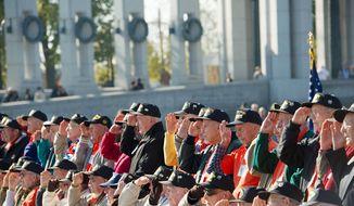 World War II veterans salute for a group photo following the Veterans Day at the National World War II Memorial event in Washington, D.C., Sunday, Nov. 11, 2012. (Rod Lamkey Jr./The Washington Times)