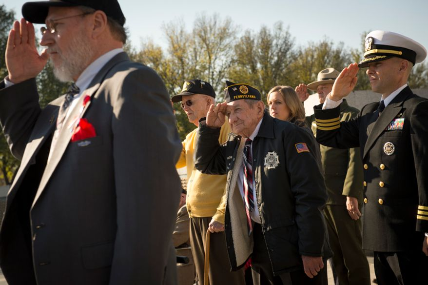 US Navy Gunner's Mate 3rd Class (Retired) Leo Stanley Zawislak [cq](center) salutes during Taps at the Veterans Day at the National World War II Memorial event in Washington, D.C., Sunday, Nov. 11, 2012. (Rod Lamkey Jr./The Washington Times)