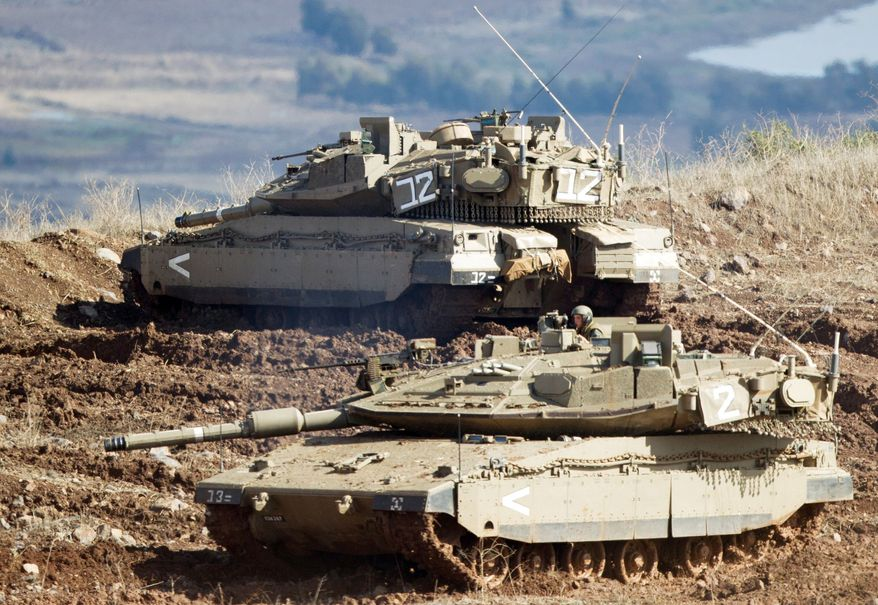Shells fired by the Syrian army explode in the Syrian village of Bariqa (top) on Monday. Israeli tanks (above) get into firing position in the Israeli-controlled Golan Heights overlooking the Syrian village. Israel said it responded to stray mortar fire from Syria. Israel has promised a tough response if the fire continues. (Associated Press)