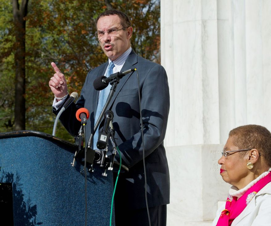 As D.C. Delegate Eleanor Holmes Norton looks on during Veterans Day observances, D.C. Mayor Vincent C. Gray urged federal law be changed so the D.C. flag can be flown at military graduations. (Barbara L. Salisbury/The Washington Times)