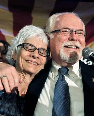 Democratic Rep. Ron Barber of Arizona hugs his wife, Nancy, on Election Day. Mr. Barber has pulled ahead of challenger Martha McSally by almost 700 votes after the Republican led by less than 500 votes in the days immediately after the election. (Associated Press)