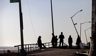 People gather on the buckled boardwalk of the Rockaway Park neighborhood in the borough of Queens in New York City on Nov. 11, 2012, in the wake of Superstorm Sandy. (Associated Press)