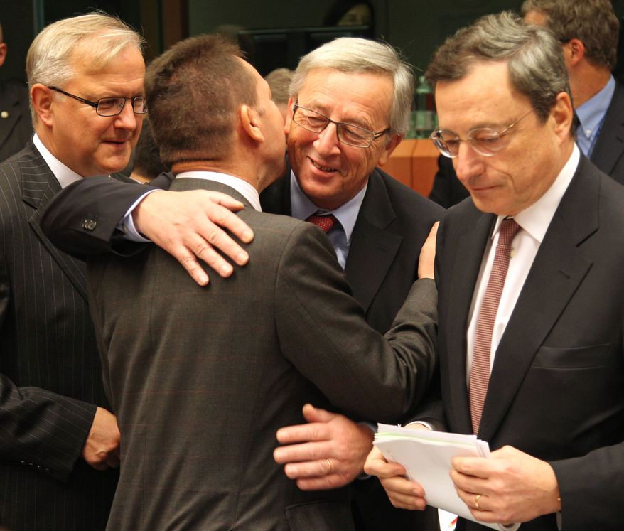 Jean-Claude Juncker (second right), Luxembourg's Prime Minister and chairman of the Eurogroup, greets Greek Finance Minister Yannis Stournaras (second left) as Olli Rehn (left), European Commissioner for Economic and Monetary Affairs, and Mario Draghi (right), President of the European Central Bank, look on Nov, 12, 2012, during the Eurogroup finance ministers meeting in Brussels. (Associated Press)