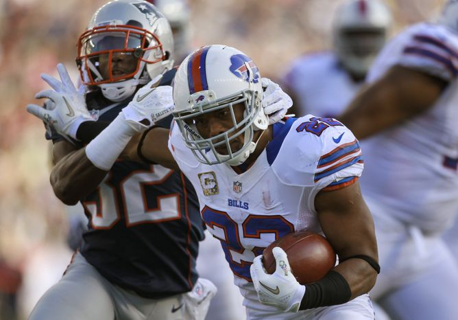 Buffalo Bills running back Fred Jackson (22), center, tries to escape the grasp of New England Patriots cornerback Devin McCourty (32), left, in the second quarter of an NFL football game at Gillette Stadium, in Foxborough, Mass., Sunday, Nov. 11, 2012. (AP Photo/Steven Senne)
