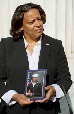 Tomi Rucker, a Washington, D.C. Navy mom, holds a picture of her son, Jonathan Matthew Rucker, at the D.C. World War I Memorial on Monday, Nov. 12, 2012. She came to the memorial to talk about the inconsistent flying of the D.C. flag at military graduations, specifically mentioning how sad she and her husband--fourth generation Washingtonians--were when the D.C. flag was not included in her son's boot camp graduation when the flags from the other recruits' states were. (Barbara L. Salisbury/The Washington Times)