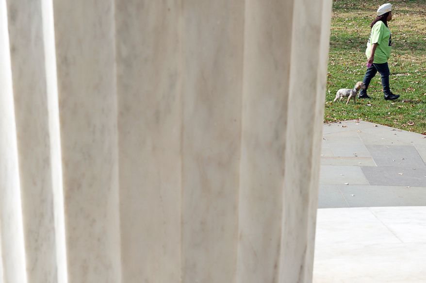 "Marilyn Wyche [cq], a D.C. resident who served in the U.S. Army at Walter Reed during Operation Desert Storm and Desert Shield, walks her dog past the D.C. World War I memorial on Monday, Nov. 12, 2012. She said she is ""grateful for the recognition"" of her service and wanted to come to the memorial on the observation of Veteran's Day. (Barbara L. Salisbury/The Washington Times)"