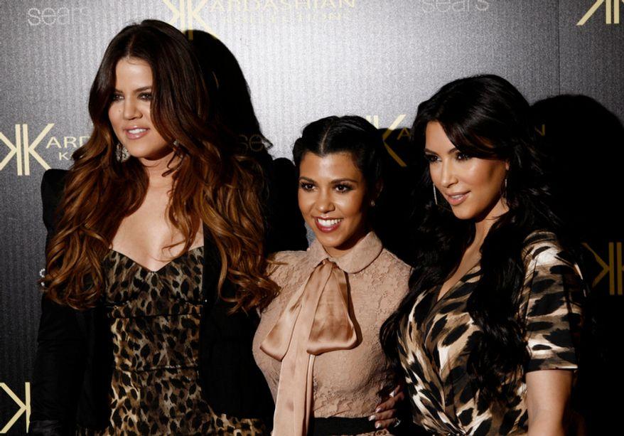 ** FILE ** Khloe Kardashian, left, Kourtney Kardashian, center, and Kim Kardashian arrive at the Kardashian Kollection launch party in Los Angeles, Wednesday, Aug. 17, 2011. The Kardashian Kollection designed by the Kardashian sisters is available at Sears. (AP Photo/Matt Sayles)
