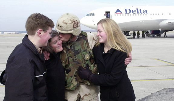 **FILE** Maj. Gen. David Petraeus (center), commanding general of the 101st Airborne Division, kisses his wife, Holly as his son, Stephen (left), and daughter, Anne, look on upon his return home from Iraq to Fort Campbell, Ky. Gen. Petraeus, the retired four-star general who led the U.S. military campaigns in Iraq and Afghanistan, resigned Friday, Nov. 9, 2012 as director of the CIA after admitting he had an extramarital affair. (Associated Press)