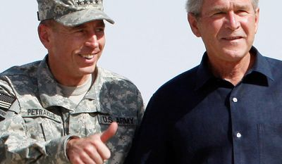 **FILE** President George W. Bush (right) stands with Gen. David Petraeus as he arrives Sept. 3, 2007, for a surprise visit at Al-Asad Airbase in Anbar province, Iraq. (Associated Press)