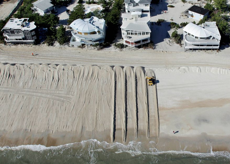 **FILE** In this aerial photograph, heavy equipment pushes sand to restore a barrier dune along the Atlantic Ocean in Harvey Cedars on Long Beach Island, N.J., on Nov. 9, 2012, after the region was pounded by Superstorm Sandy the previous week. (Associated Press)