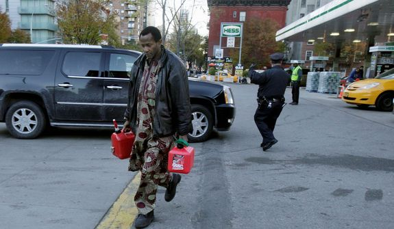 **FILE** A man carries two filled gas cans at a New York gasoline station on Nov. 9, 2012. A new gasoline rationing plan that lets motorists fill up every other day went into effect in New York that morning after Superstorm Sandy hit the region. Police were at gas stations to enforce the new system in New York City and on Long Island. (Associated Press)